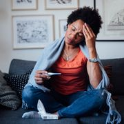 worried african american woman sitting at home while being sick