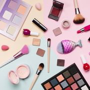 set of decorative cosmetics on pastel pink, yellow and blue background flat lay style