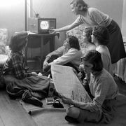 women watching television and reading a newspaper