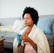 african american woman, fallen ill is staying at home wrapped in a blanket socially distancing and quarantining herself, feeling her throat hurt and being sore, having a cup of hot tea