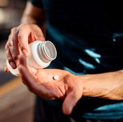 close up of human hands man holding the medicine bottle in one hand and pill in other