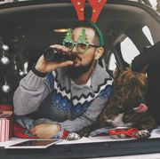 bearded man and his dog celebrating christmas they are lying and man using digital tablet and drinking beer