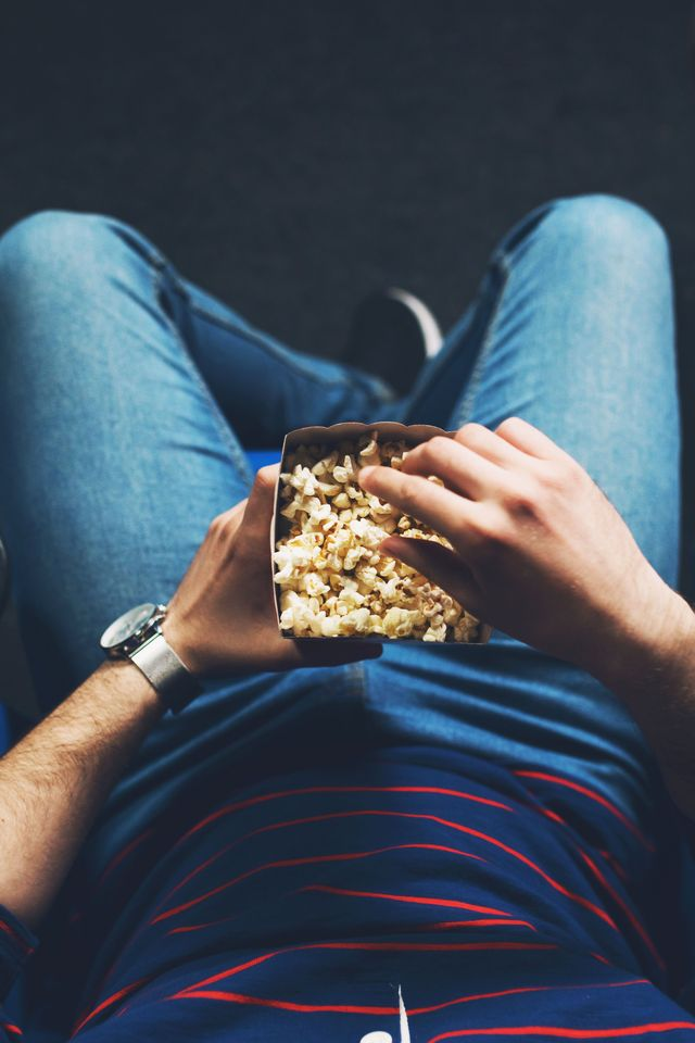 man eating popcorn in theater