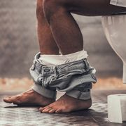 close up handsome young afro american man sitting on toilet in bathroom at morning personal morning routine fresh and relax at morning guy near mirror hygiene at morning concept