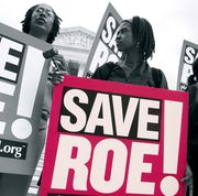 a woman holding a sign that says save roe