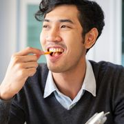 young college students adult male sat eating snack with happiness in room