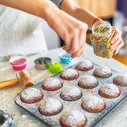 baker adding sprinkles to cupcakes