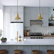 gray and white kitchen with brass pendants