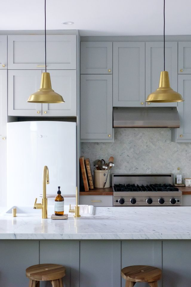 gray kitchen with brass pendants