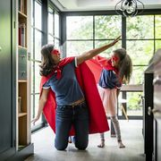 girl with mother in red superhero costume at home