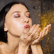 woman with shimmer eyeshadow blowing on gold glitter