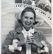 gloria in a chair with her hands connected in the air