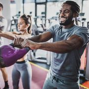 group of athletes exercising with kettle bells on cross training in a gym