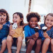 group of cheerful multiethnic children eating icecream in summer