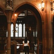 woman walking in spooky gothic library