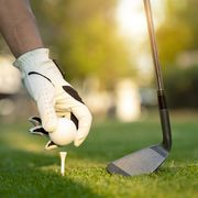 hand asian woman putting golf ball on tee with club in golf course on evening and sunset time a for healthy sport lifestyle concept