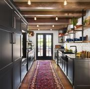 galley kitchen with white walls, black cabinets, wood floors and red runner rug facing french doors to the outside