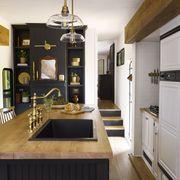kitchen, camper, black kitchen island with wooden countertop, gold hardware, white storage units