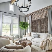 owners den, brick wall, white lounge sofa, white lounge chairs, throw rug, white and cream decorative cushions, gray walls, gray curtains, black candle ceiling light