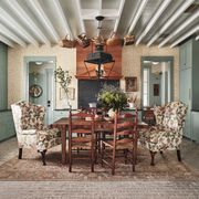 green kitchen, green cabinets, floral dining chairs, wooden table and wooden dining chairs, weaving baskets, wooden ceiling beams