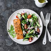 healthy mediterranean lunch   grilled fillet salmon and vegetables, olives, feta greek salad on dark background, top view