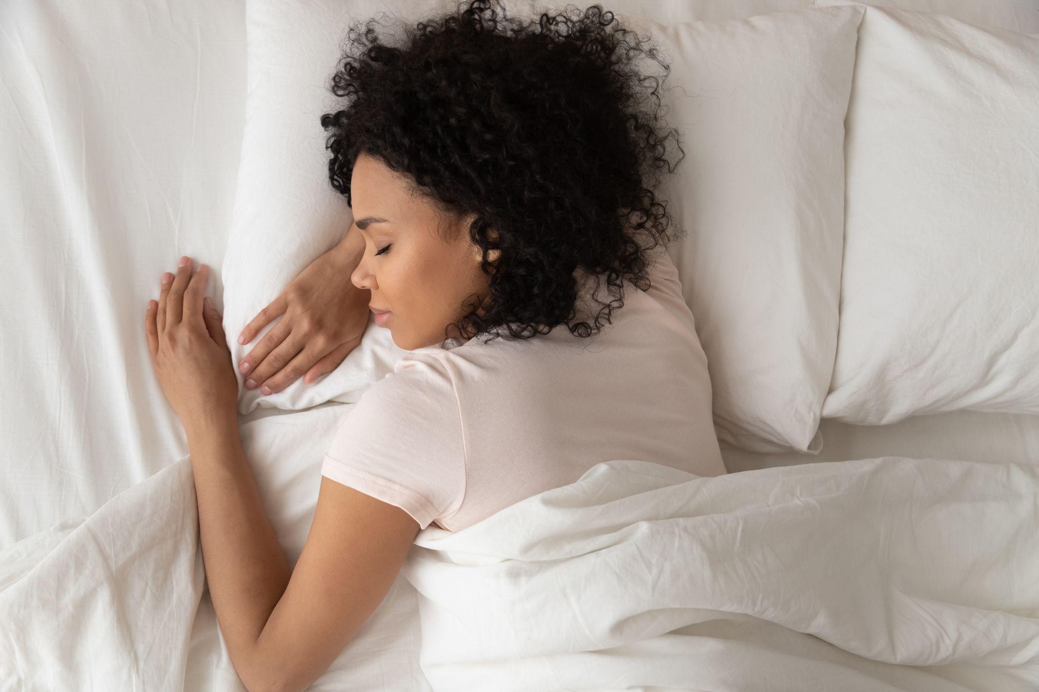 Healthy serene african girl sleeping in comfortable bed, top view