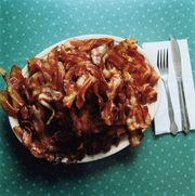 heaping plate of fried bacon on table, closeup