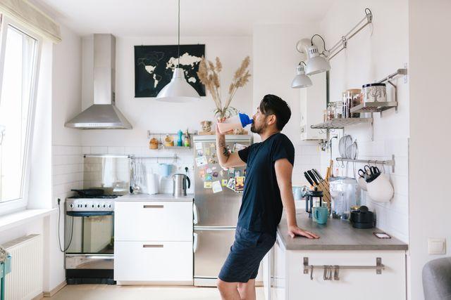 man in sportkleding staat in keuken en drinkt een eiwitshake na het trainen