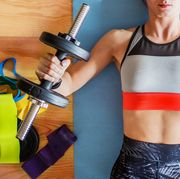 above photo of woman at home in sports bra and leggings lying on yoga mat lifting weights surrounded by resistance bands