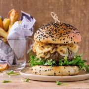 Homemade burgers with beef, fried onion and pea sprouts, served on ceramic plate with fried potatoes over wooden textured background