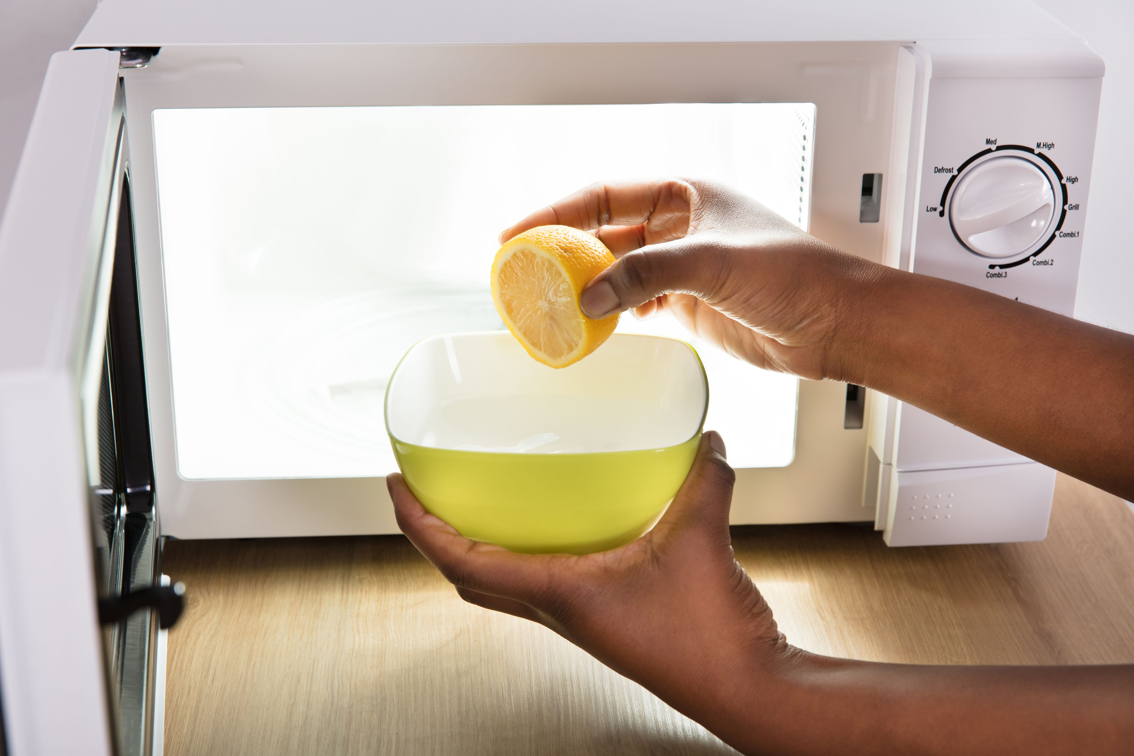 Human Hand Putting Sliced Lemon In Bowl