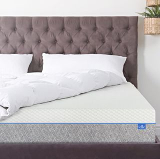 bed with sheets turned up to show mattress
