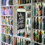 "a community in williamsburg, virginia creates a ""stay at home"" art installation built by resident painted wine bottles"