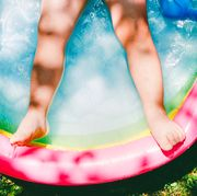 childs legs in colorfulinflatable pool on grasssurrounded by pool toys