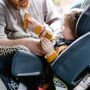 dad strapping kid into car seat