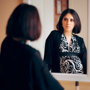 introspective pregnant woman analyzing herself in a mirror