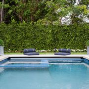 pool with floor cushions and hedges