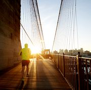 jogger in bright jacket running into the sunset on brooklyn bridge