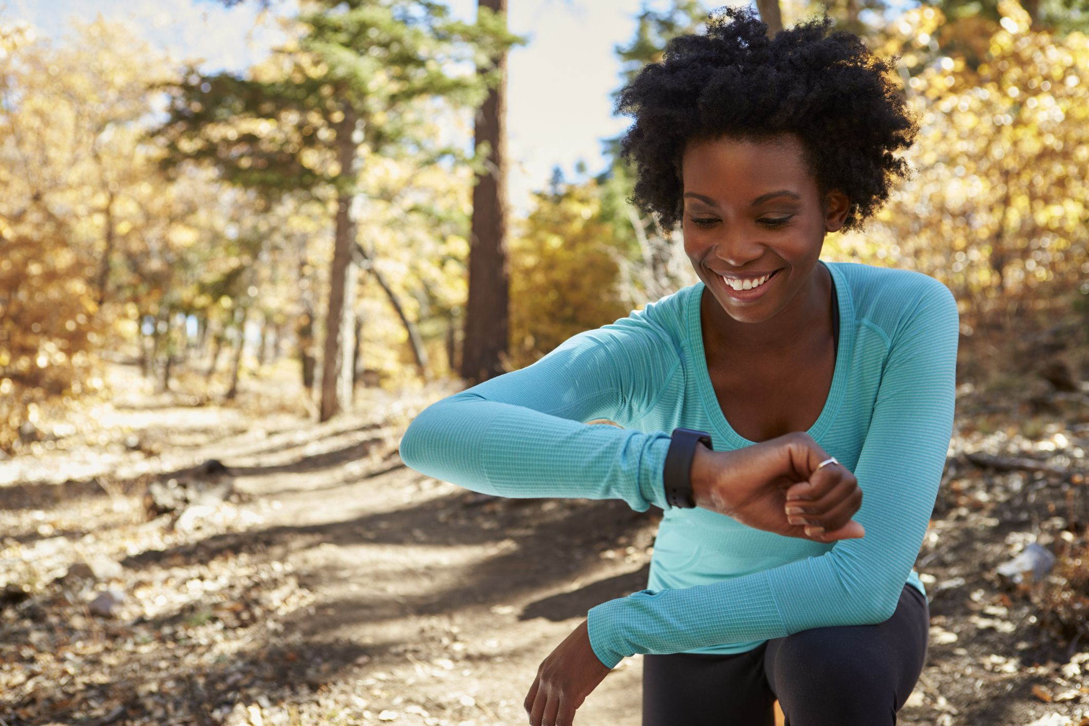 Young black woman in a forest checking smartwatch and smiling