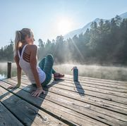 jogging woman relaxing on lake pier at sunrise enjoying freshness from nature
