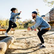 kid in jean jacket jumping to dad on playground