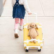 girl pulling kids luggage with stuffed animal