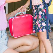 mom handing red lunch box to daughter