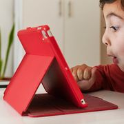 kid playing with tablet in red case