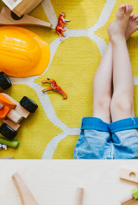 kids in playroom with toys scattered on floor