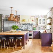 kitchen with purple cabinets and wallpaper