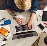 woman working at desk on laptop with external hard drive and smartphone