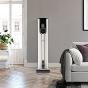 lg silver and cordless vacuum with docking station set against gray wall of living room with gray couch