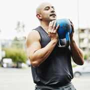man doing kettlebell squats during workout at outdoor gym