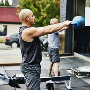 man doing kettlebell swings while working out at outdoor gym